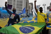 People raise their clenched fists as they demonstrate with a Brazilian flag against Brazilian President Jair Bolsonaro and racism, in Sao Paulo, Brazil, on June 14, 2020, amid the novel coronavirus pandemic. (Photo by NELSON ALMEIDA / AFP)