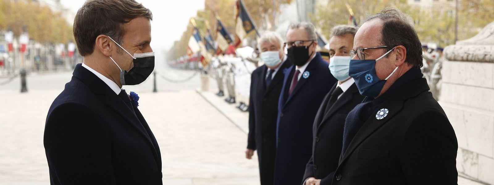 Emmanuel Macron begrüßt seinen Amtsvorgänger François Hollande während der Gedenkzeremonie am Triumphbogen in Paris.
