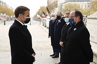French President Emmanuel Macron (L) salutes French former President Francois Hollande (R) as he attends a ceremony at the Arc de Triomphe in Paris on November 11, 2020, as part of the commemorations marking the 102nd anniversary of the November 11, 1918 Armistice, ending World War I (WWI). (Photo by Yoan VALAT / POOL / AFP)