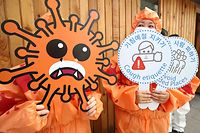 Members of the Asian Citizen's Center for Environment and Health wearing masks depicting the coronavirus perform during a campaign for preventative measures against the COVID-19 coronavirus, in Seoul on March 26, 2020. - US President Donald Trump has requested novel coronavirus test kits from South Korea, his counterpart Moon Jae-in said March 25, as Washington pushes for a quick reopening of the world's biggest economy. (Photo by - / YONHAP / AFP) / - South Korea OUT / REPUBLIC OF KOREA OUT  NO ARCHIVES  RESTRICTED TO SUBSCRIPTION USE