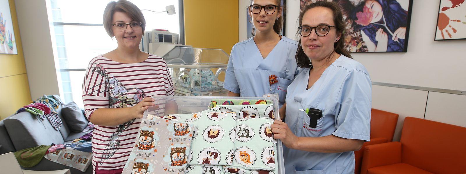 Nadine Zeitz-Mousel und die Kinderkrankenschwestern Nathalie Lux und Barbara Tasch (v.l.n.r.) aus dem CHL mit einer Kiste voller neuer Babydecken.