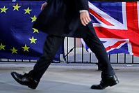 "(FILES) In this file photo taken on February 12, 2019 A man walks past the EU and Union flags of anti-Brexit protesters outside the Houses of Parliament in London. - British Prime Minister Boris Johnson thinks his talks with the EU will fail and that he will then have to ""do all sorts of things"" to prevent another Brexit delay, a government official told The Spectator magazine. But should an extension still be granted at next week's EU summit, Johnson will not re-submit his current proposal, the source in Johnson's Downing Street office said on October 8, 2019. (Photo by Tolga AKMEN / AFP)"