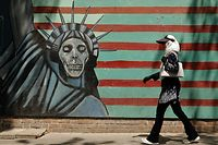 "An Iranian woman walks by a mural on the wall of the former US embassy in the Iranian capital Tehran on August 7, 2018. US President Donald Trump warned countries against doing business with Iran today as he hailed the ""most biting sanctions ever imposed"", triggering a mix of anger, fear and defiance in Tehran. / AFP PHOTO / ATTA KENARE"