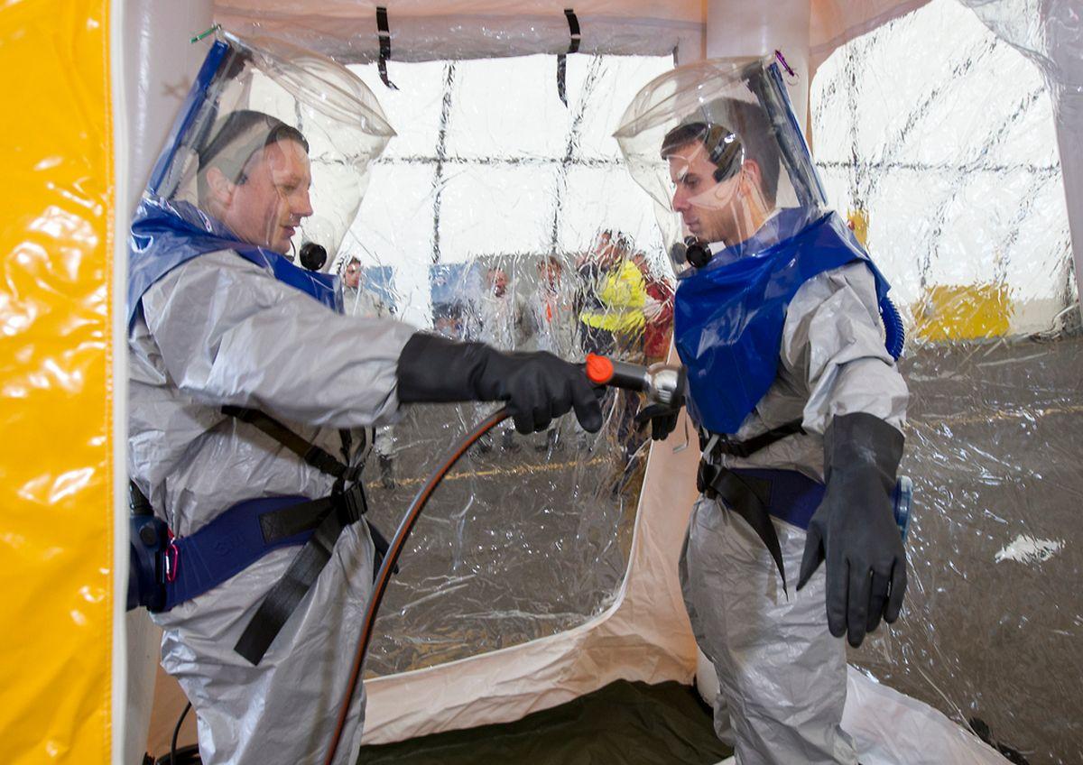 Bei einem Pressetermin zeigten zwei Hilfskräfte, wie nach einem Ebola-Einsatz die Einweg-Schutzanzüge mit einem Desinfektionsmittel abgespritzt werden.