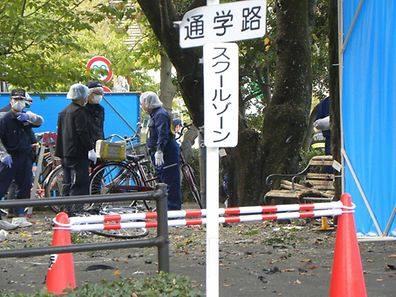 Policemen investigate an explosion site at a park in Utsunomiya, some 100 kilometres (60 miles) north of Tokyo on October 23, 2016. One person was killed and at least two injured by two near-simultaneous blasts in a Japanese park on October 23, the local fire department said. / AFP PHOTO / JIJI PRESS / JIJI PRESS / Japan OUT