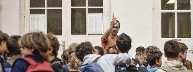 Un instituteur guide ses élèves vers la salle de classe dans une école élémentaire à Paris en ce jour de la Rentrée 2014-2015.