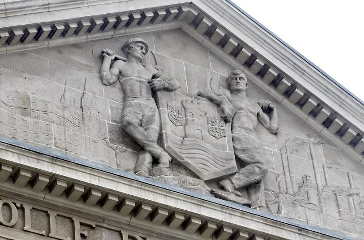 A miner and a steel worker flank the crest of the city of Esch on the town hall Photo: Guy Jallay