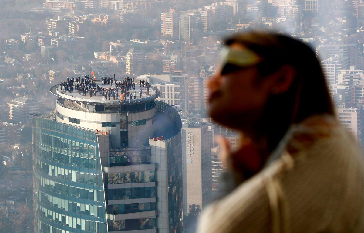 Zahlreiche Schaulustige beobachten den Himmel auf der Terrasse eines Hochhauses in Santiago de Chile, während sie auf die Sonnenfinsternis warten.