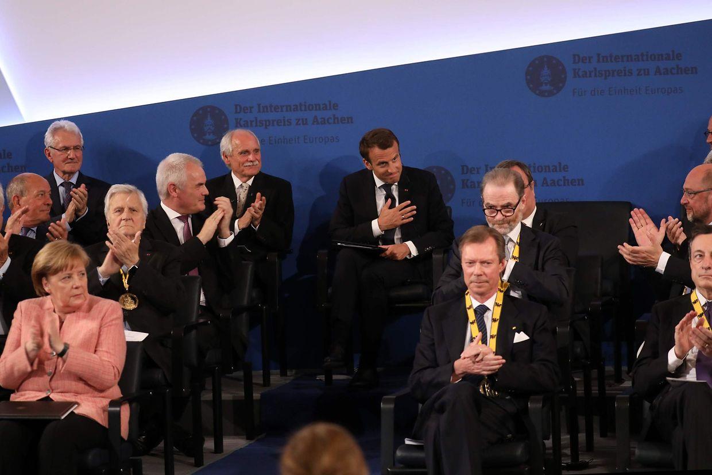 Au premier rang, Angela Merkel et le grand-duc henri, applaudissant Emmanuel Macron, en arrière plan
