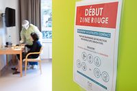 Retirement home's staff, wearing protective clothe and mask, helps a resident in a room with an entrance sign reading 'red zone starts here' in Vottem on November 10, 2020 as the country is facing a second wave of the covid-19 pandemic caused by the novel coronavirus. (Photo by BENOIT DOPPAGNE / Belga / AFP) / Belgium OUT
