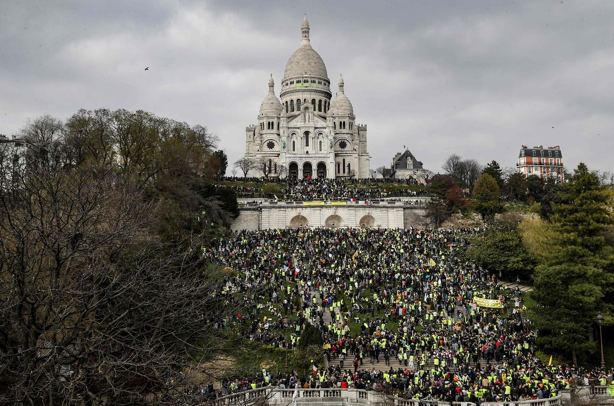 "Yellow Vest protesters gather in front of the Sacre Coeur Basilica ontop of the Montmartre hill in Paris on March 23, 2019, during an anti-government demonstration called by the 'Yellow Vest' (gilets jaunes) movement. - Demonstrators hit French city streets again on March 23, for a 19th consecutive week of nationwide protest against the French President's policies and his top-down style of governing, high cost of living, government tax reforms and for more ""social and economic justice."" (Photo by Geoffroy VAN DER HASSELT / AFP)"