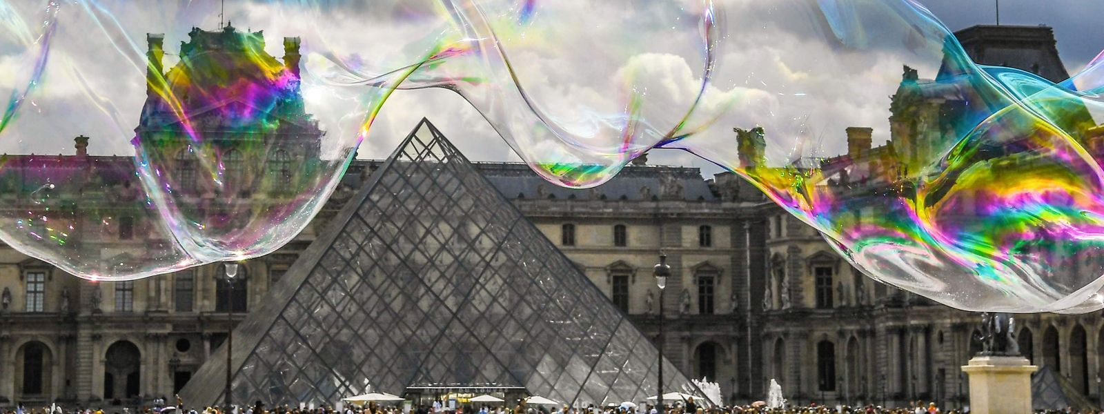 The Louvre pyramid in front of the Louvre museum in Paris is seen through soap bubbles on July 19, 2019. (Photo by ALAIN JOCARD / AFP)