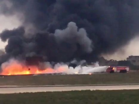 Still image taken from video shows fire trucks aiming their hoses at the burning wreckage of a small plane which crashed at the edge of the runway at the airport in Valletta, Malta, 24 October 2016.   REUTERS/Ed De Gaetano via Reuters TV    NO SALES. NO ARCHIVES. FOR EDITORIAL USE ONLY. NOT FOR SALE FOR MARKETING OR ADVERTISING CAMPAIGNS.