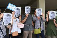 """Kassel: Demonstranten gegen den Aufmarsch der Kleinstpartei """"Die Rechte"""" halten sich Porträts des erschossenen Walter Lübcke vor das Gesicht. Die Partei hatte dazu aufgerufen, in Kassel im Zusammenhang mit dem Fall Lübcke gegen mediale Vorverurteilung zu demonstrieren."""