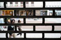 19.08.2021, Hessen, Frankfurt/Main: Menschen gehen hinter dem Gitter eines leerstehenden Geschäfts in der Innenstadt vorbei. Foto: Sebastian Gollnow/dpa +++ dpa-Bildfunk +++