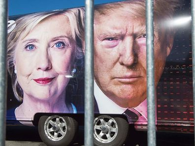 Large images of Democratic nominee Hillary Clinton and Republican nominee Donald Trump are seen on a CNN vehicle, behind a security fence, on September 24