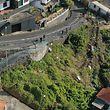 dpatopbilder - HANDOUT - 18.04.2019, Portugal, Canico: Die Stelle, an der am Vortag ein schweres Busunglück auf der portugiesischen Ferieninsel Madeira stattfand, ist zur Straße hin abgesperrt. Bei dem Busunglück auf der portugiesischen Atlantikinsel Madeira sind 29 Menschen ums Leben gekommen. Unter den Opfern sind nach bisherigen Erkenntnissen wahrscheinlich viele deutsche Urlauber. (Luftaufnahme mit Drohne) Foto: Andriy Petryna/dpa +++ dpa-Bildfunk +++