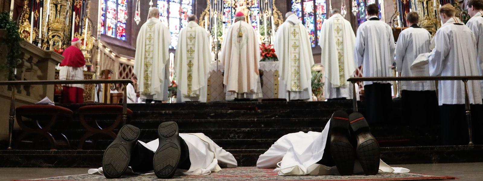 Während die versammelte Kirchengemeinschaft Maria und die Kirchenheiligen anrufen, liegen Vincent De Smet und Yves Olinger auf dem Boden vor dem Votivaltar.