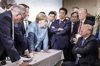 HANDOUT - 09.06.2018, Charlevoix, La Malbaie, Quebec, Kanada: Bundeskanzlerin Angela Merkel (CDU, M) spricht mit US-Präsident Donald Trump (r) während der Beratungen am Rande der offiziellen Tagesordnung. Emmanuel Macron (2.v.l), Präsident von Frankreich, Shinzo Abe (4.v.r), Ministerpräsident von Japan, und John Bolton, Nationaler Sicherheitsberater der USA, verfolgen das Gespräch. Foto: Jesco Denzel/Bundesregierung /dpa - ACHTUNG: Nur zur redaktionellen Verwendung und nur mit vollständiger Nennung des vorstehenden Credits +++ dpa-Bildfunk +++