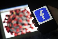 (FILES) In this file photo taken on March 24, 2020 a Facebook logo is displayed on a mobile phone screen next to a coronavirus COVID-19 illustration in Arlington, Virginia. - Facebook on April 29, 2020 reported a sharp jump in usage as the global pandemic unfolded, in a quarterly update that sparked a rally in shares of the social network despite its warning of turbulence in the coming months. (Photo by Olivier DOULIERY / AFP)