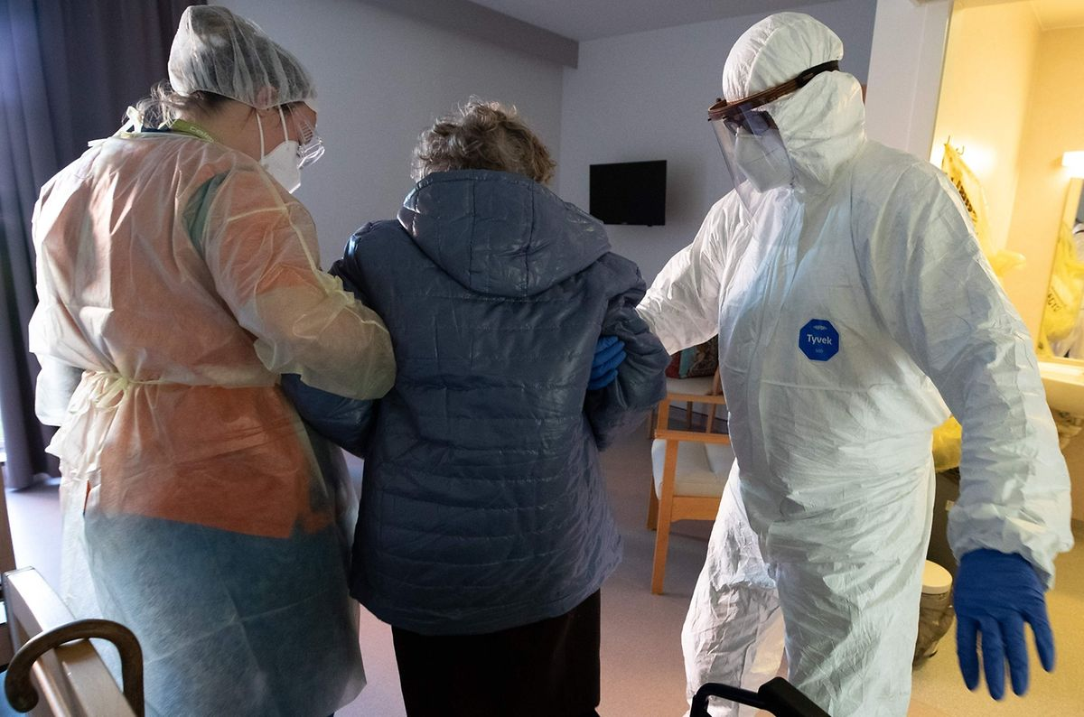 Staff in protective gear at a care home in Belgium helping an elderly woman Photo: AFP
