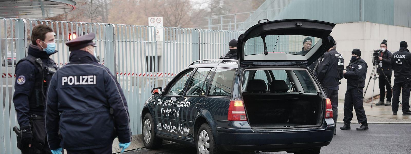 Ein Auto steht vor dem Tor des Bundeskanzleramts. Auf der Seite des augenscheinlich unbeschädigten dunklen Kombis steht in weißer Schrift eine Beschimpfung geschrieben: «Ihr verdammten Kinder und alte Menschen-Mörder».