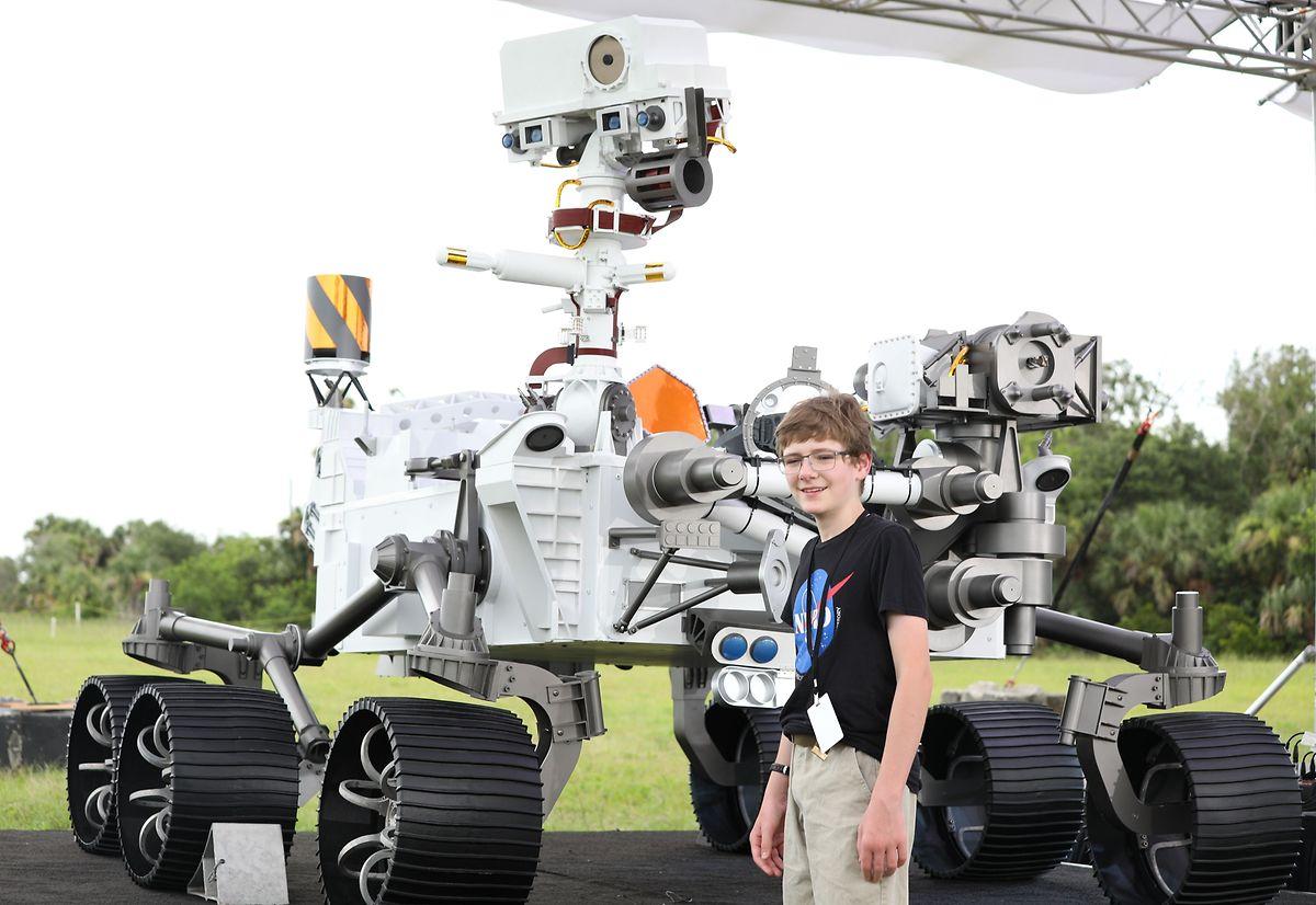 Alex Mather, um jovem norte-americano de treze anos em frente a uma maquete em tamanho real do robô Perseverance em Cape Canaveral, na Florida. Mather deu o nome ao robô.