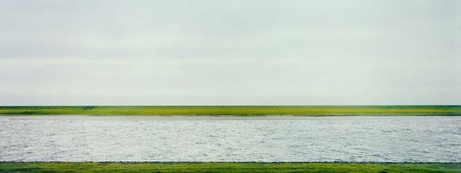 """Ein grauer Strom fließt durch eine aseptische Landschaft: """"Rhein II"""" von Andreas Gursky."""