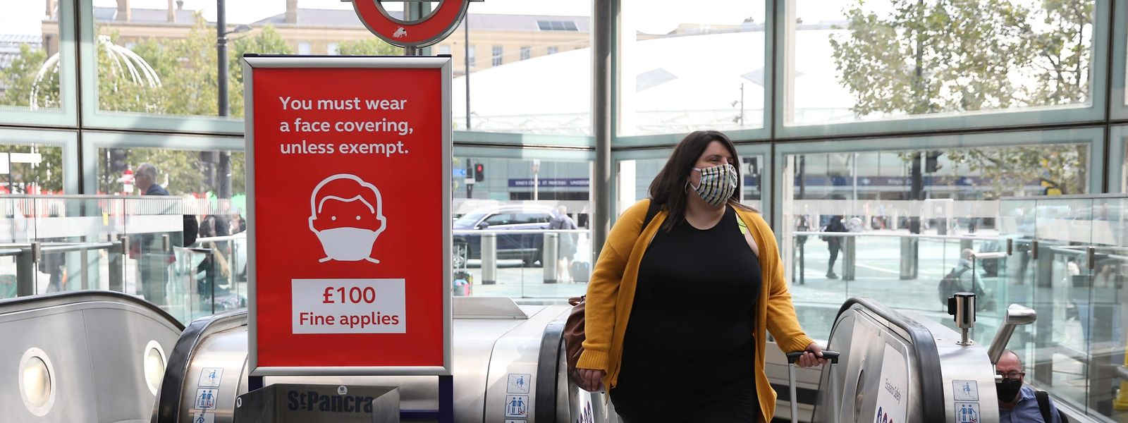 A woman wearing a protective face covering passes a poster warning of fines for not wearing face coverings as she steps off the escalator at St Pancras station in London on September 11, 2020. (Photo by ISABEL INFANTES / AFP)