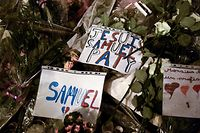 "Flowers and signs reading ""I am Samuel Paty' are displayed at a makeshift memorial during a march (marche blanche) in Conflans-Sainte-Honorine, northwest of Paris, in tribute to French teacher Samuel Paty who was beheaded for showing cartoons of the Prophet Mohammed in his civics class. - Paty, 47 years-old, was attacked on October 16 on his way home from the junior high school where he taught by 18-year-old Chechen man Abdullakh Anzorov, who was shot dead by police. Following the attack, tens of thousands of people took part in rallies countrywide to honour Paty and defend freedom of expression. (Photo by Bertrand GUAY / AFP)"
