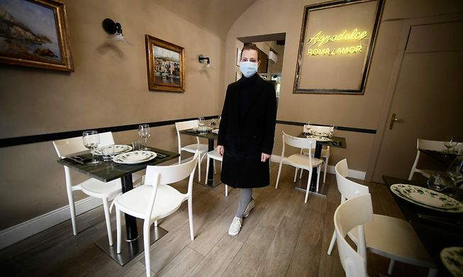 A worker prepares for the reopening of a restaurant despite restrictions which only allow to offer takeaway services on the sidelines of a demonstration of independent workers who protest against Covid-19 restrictions, near the Trevi fountain in downtown Rome on April 8, 2021.