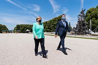 German Chancellor Angela Merkel and Bavaria's State Premier and leader of the Bavarian Christian Social Union (CSU) Markus Soeder wear face masks as they walk to the castle on Herrenchiemsee island, Bavaria, on July 14, 2020. - Chancellor Angela Merkel will attend the Bavarian cabinet meeting in the Mirror Gallery of the New Palace of Herrenchiemsee. (Photo by Peter Kneffel / POOL / AFP)