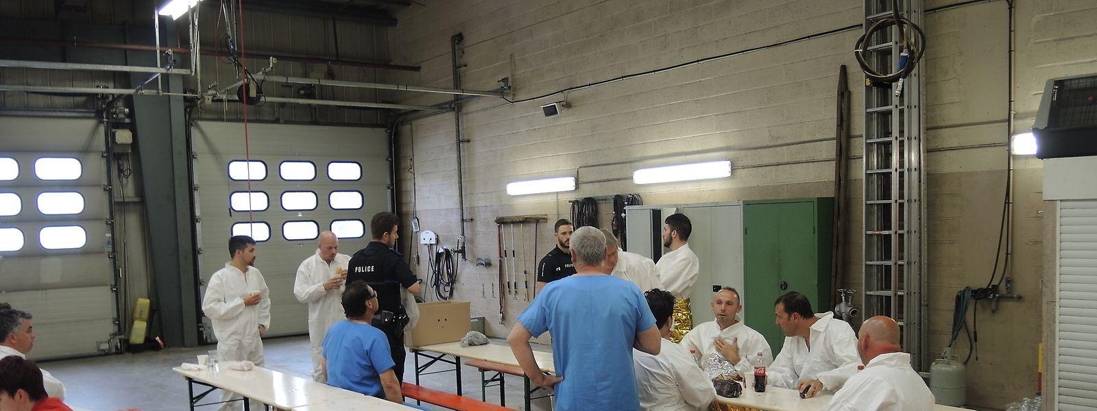 In weißen Schutzanzügen gekleidet, warten die ArcelorMittal-Mitarbeiter in der Differdinger Kaserne auf ihre Habseligkeiten.