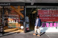 A shopper makes his way into a store offering a closing down sale in Auckland on June 19, 2020. - New Zealand's economy suffered its biggest contraction in 29 years during the first three months of the year, official data showed, with worse expected as the coronavirus pandemic's full impact emerges. (Photo by GREG BOWKER / AFP)