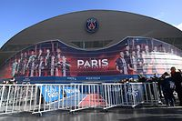 TOPSHOT - People stand next to barriers set up to prevent contact between players and supporters amid fear of Covid-19 (novel Coronavirus) at the Parc des Princes stadium in Paris, on February 29, 2020 before the Ligue 1 football match between Paris Saint-Germain and Dijon. (Photo by FRANCK FIFE / AFP)