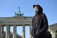 """A protester, wears a face mask bearing the words """"leave no one behind, during a nationwide action under the moto �Wir hinterlassen Spuren - #LeaveNoOneBehind� to protest against Europe external borders and asking to prevent a """"corona catastrophe"""" on April 5, 2020 in front of the landmark Brandenburg Gate in Berlin, amid the new coronavirus COVID-19 pandemic. (Photo by Tobias SCHWARZ / AFP)"""