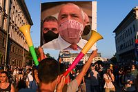 A protestor holds a collage mocking the Bulgarian Prime minister wearing a protective mask  made of a 500 euros bill during an anti-government protest in Sofia, on July 29, 2020, as thousands of people have been demanding for weeks, for the resignation of the government which they accuse of protecting the oligarchy. (Photo by NIKOLAY DOYCHINOV / AFP)