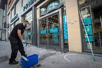 A worker cleans windows of a clothes shop with social distancing markings on the pavement outside in the rue Neuve - Nieuwstraat shopping street in the city centre of Brussels, on May 9, 2020, as Belgium prepares to ease measures following eight weeks of lockdown aimed at curbing the spread of the COVID-19 pandemic, caused by the novel coronavirus. - Shops will be allowed to reopen and more people return to work in Belgium starting May 11, 2020. (Photo by VIRGINIE LEFOUR / BELGA / AFP) / Belgium OUT