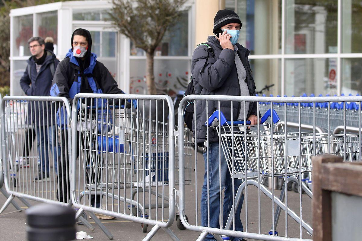 Kunden mit Schutzmasken warten in Großbritannien vor einem Supermarkt.
