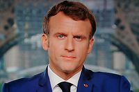 French President Emmanuel Macron is seen on a TV screen as he speaks during a televised address to the nation from the temporary Grand Palais in Paris on July 12, 2021. - Macron announced  mandatory Covid jabs for healthcare staff and that 'Covid pass' will be needed in restaurants from August. (Photo by Ludovic MARIN / AFP)