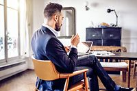 bearded business man reading on mobile in home office