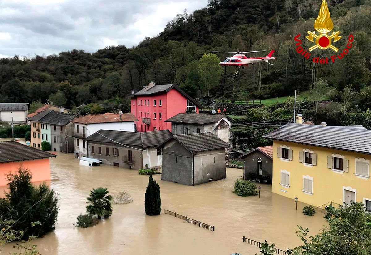 Italien, Ornavasso: Ein Feuerwehrhubschrauber überfliegt eine überschwemmte Stadt  in der norditalienischen Region Piemont.