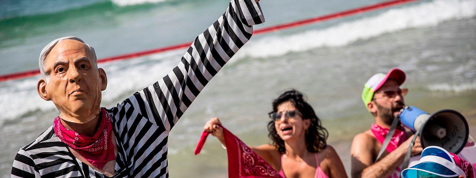 Mit einer Maske von Premierminister Netanjahu nimmt ein Mann an einem Protest gegen weitere Corona-Maßnahmen am Strand von Tel Aviv teil.