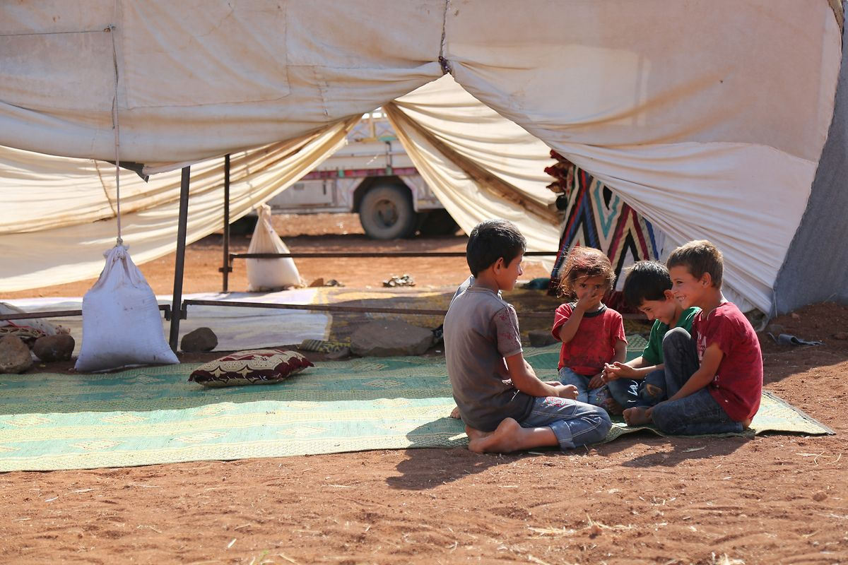 Kinder sitzen vor ihrem Zelt in einem provisorischen Flüchtlingslager. Die Flüchtlinge mussten wegen andauernder Angriffe einige Flüchtlingslager in der Provinz Idlib verlassen.