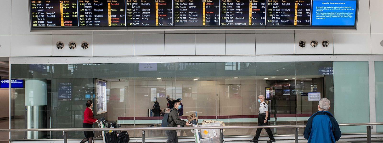 Reisende tragen Schutzmasken am Hongkong international Flughafen.