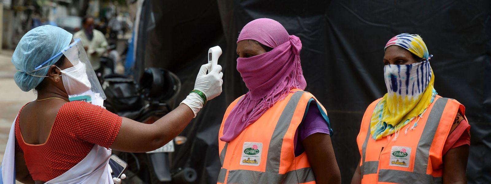 Eine indische Gesundheitspflegerin kontrolliert die Körpertemperatur von möglichen Covid-19-Erkrankten.