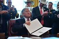 US President Donald Trump displays his veto in response to the congressional rebuke on border emergency at the Oval Office of the White House in Washington, DC, March 15, 2019. (Photo by Nicholas Kamm / AFP)