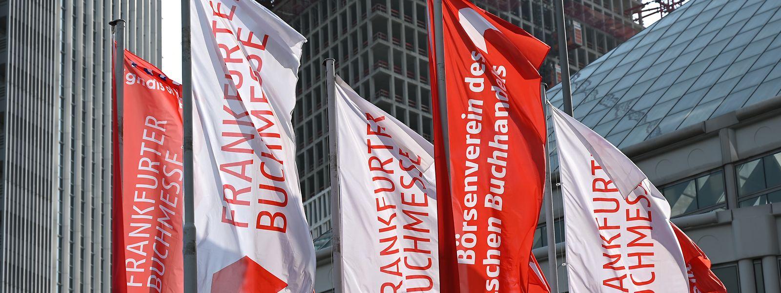 """Fahnen mit der Aufschrift """"Frankfurter Buchmesse"""" und """"Börsenverein des Deutschen Buchhandels"""" wehen vor dem Eingang City des Messegeländes. Die «Sonderedition» der Buchmesse findet vom 14. bis 18. Oktober statt."""