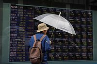 A man looks at an electronic stock quotation board of the Tokyo Stock Exchange in Tokyo on May 18, 2020. - Japan dived into its first recession since 2015, according to official data on May 18, with the world's third-largest economy shrinking by 0.9 percent in the first quarter as it wrestles with the fallout from the coronavirus. (Photo by Kazuhiro NOGI / AFP)