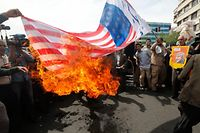 TOPSHOT - Iranians set fire to a makeshift US flag during a demonstration after Friday prayer in the capital Tehran on May 11, 2018. Iran's foreign minister will embark on a diplomatic tour to try to salvage the nuclear deal amid high tensions following the US withdrawal and global fears over reports of unprecedented clashes with Israel in Syria. / AFP PHOTO / STRINGER